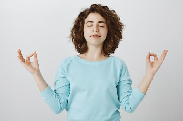Vreedzame en ontspannen glimlachende vrouw die met gesloten ogen mediteert om zen te vinden
