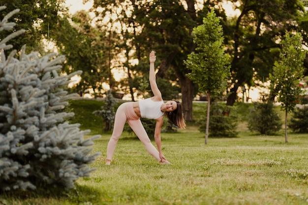 Vreedzame, fitte vrouw staat in driehoekshouding en doet yoga bij zonsondergang in het park in de zomer, concept van meditatie en contemplatie.
