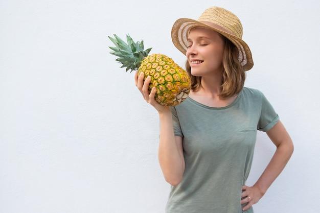 Vreedzame geïnspireerde vrouw in zomerhoed ruiken hele ananas