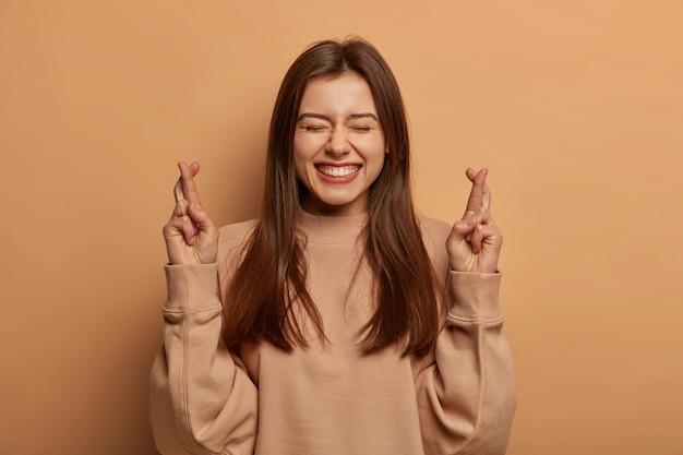 Vreedzame, gelukkige vrouw kruist vingers voor geluk, gelooft hopelijk in geluk, verwacht dat dromen uitkomen, lacht breed, draagt bruine sweater