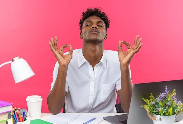 Vreedzame jonge afro-amerikaanse student zit aan bureau met schoolhulpmiddelen mediteren geïsoleerd op roze muur