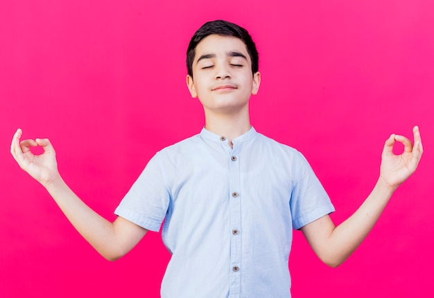 Vreedzame jonge blanke jongen mediteren met gesloten ogen geïsoleerd op een karmozijnrode achtergrond