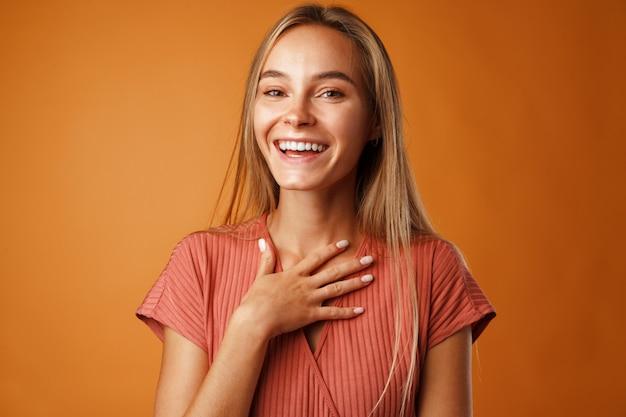 Vreedzame jonge blonde vrouw hand in hand op haar borst