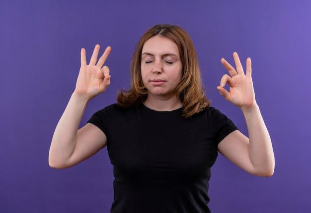 Vreedzame jonge casual vrouw doet ok teken met gesloten ogen op geïsoleerde paarse ruimte