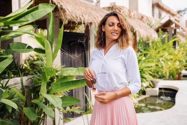Vreedzame jonge gelukkige vrouw met kort krullend haar in roze lange rok en wit overhemd alleen buiten haar villa
