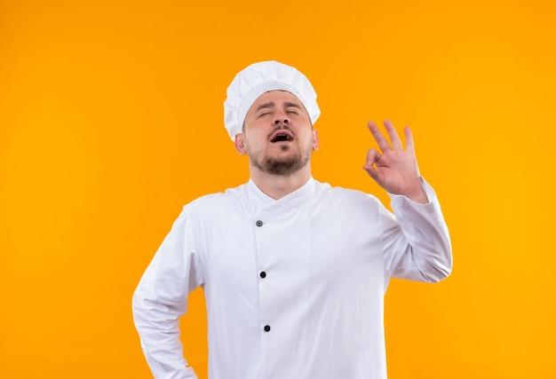 Vreedzame jonge knappe kok in eenvormige chef-kok die ok teken met gesloten ogen en open mond op geïsoleerde oranje ruimte doet