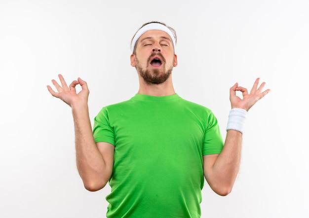 Vreedzame jonge knappe sportieve man met hoofdband en polsbandjes doen ok tekenen met gesloten ogen en open mond geïsoleerd op witte ruimte