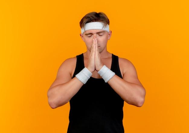 Vreedzame jonge knappe sportieve man met hoofdband en polsbandjes handen aanbrengend bidden gebaar in de buurt van gezicht met gesloten ogen geïsoleerd op een oranje achtergrond