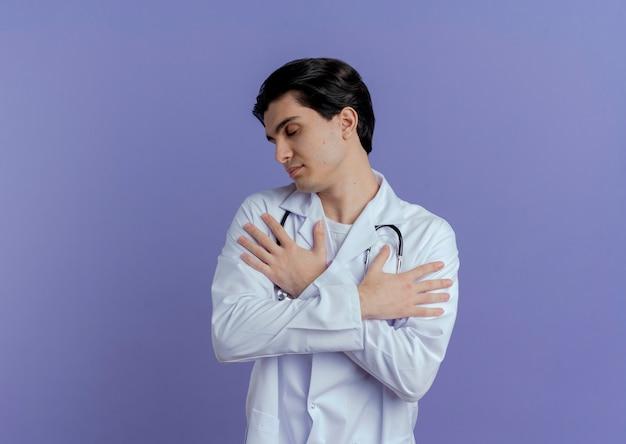 Vreedzame jonge mannelijke arts die medische mantel en stethoscoop draagt die handen op wapens houdt die met geïsoleerde gesloten ogen hoofd aan zij draaien