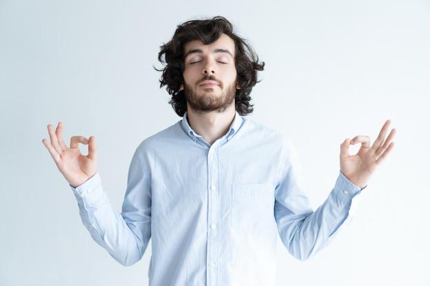 Vreedzame jonge mens die met zijn gesloten ogen mediteert