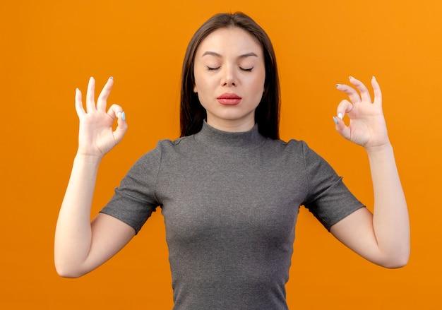 Vreedzame jonge mooie vrouw mediteren met gesloten ogen geïsoleerd op een oranje achtergrond