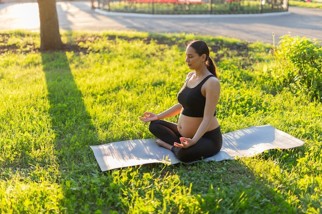 Vreedzame jonge positieve zwangere vrouw in gymnastiek pak doet yoga en mediteren zittend op de mat op groen gras op zonnige warme zomerdag. concept voorbereiding op de bevalling en een positieve houding