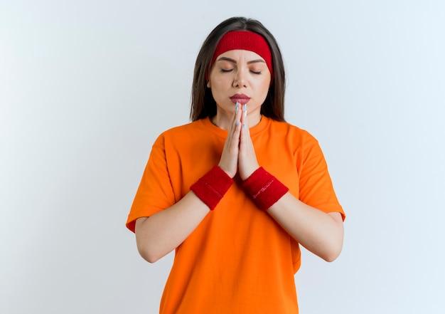 Vreedzame jonge sportieve vrouw die hoofdband en polsbandjes draagt die handen samenbrengen biddend met gesloten ogen die op witte muur met exemplaarruimte worden geïsoleerd
