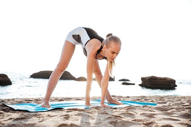 Vreedzame jonge vrouw die ontspannende yoga-oefeningen buitenshuis doet