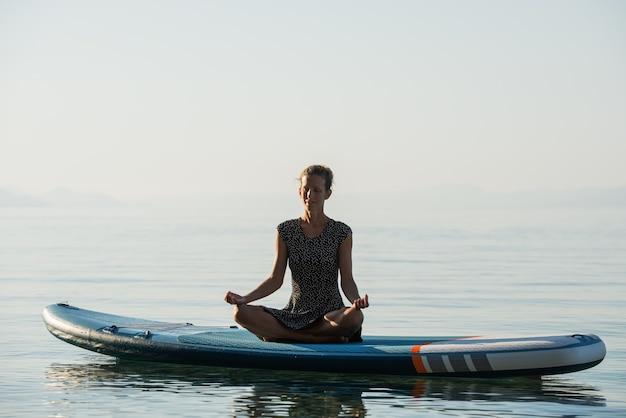 Vreedzame jonge vrouw met een serene uitdrukking op haar gezicht mediterend in lotushouding op een sup board drijvend op het water.