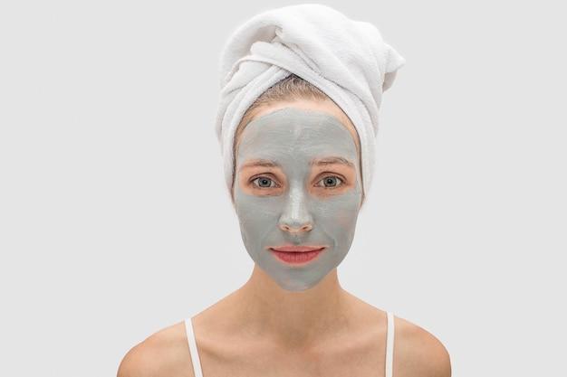 Vreedzame jonge vrouw staat en kijkt. haar gezicht is bedekt met moddermasker. model is kalm. witte handdoek bedekt haar haar.