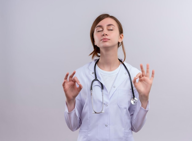 Vreedzame jonge vrouwelijke arts die medische mantel en stethoscoop draagt die ok teken met gesloten ogen met exemplaarruimte doen