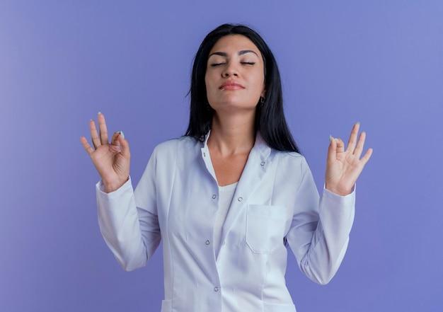 Vreedzame jonge vrouwelijke arts die medische robe draagt die met gesloten ogen mediteren