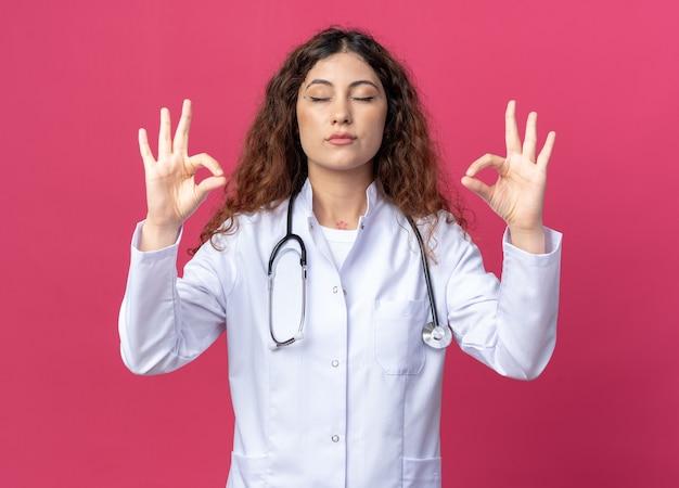 Vreedzame jonge vrouwelijke arts met een medisch gewaad en een stethoscoop die mediteert met gesloten ogen geïsoleerd op een roze muur