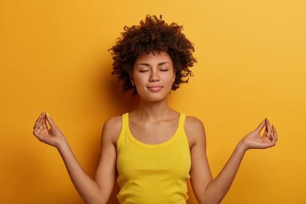 Vreedzame kalme gekrulde vrouw staat in lotushouding, bereikt nirvana, beoefent yoga of meditatie, houdt de ogen dicht, gekleed in vrijetijdskleding, geïsoleerd over gele muur, maakt oké of zen-teken