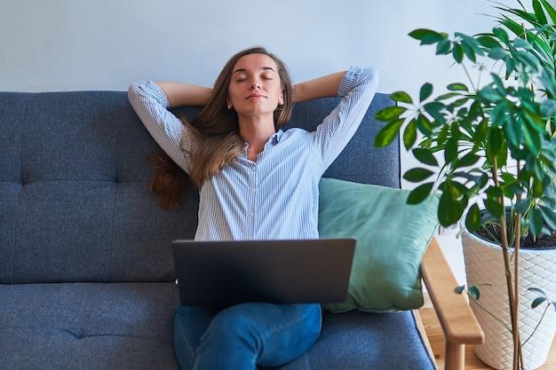 Vreedzame kalme vrouw met handen achter hoofd alleen rusten op comfortabele bank met computer op knieën op gezellige comfortabele woonkamer thuis onder planten binnenshuis