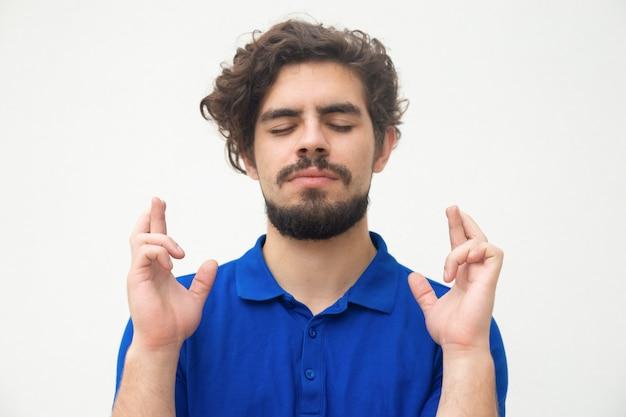 Vreedzame kerel met gesloten ogen die vingers gekruist houden
