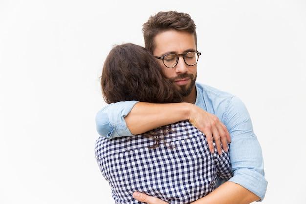 Vreedzame knappe man met gesloten ogen knuffelen vriendin
