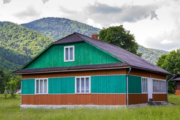 Vreedzame landelijke zomer landschap op zonnige dag. verlicht door de zon prachtige houten woonhuis geschilderd in groene, blauwe en bruine kleuren op met gras begroeide bloeiende weide op beboste bergen.