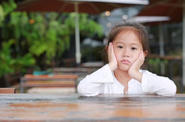 Vreedzame leuke kleine aziatische kind meisje liggend op de houten tafel met je op zoek.