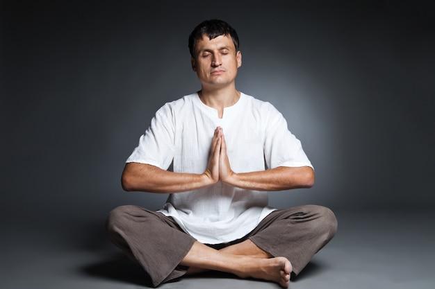 Vreedzame man die yoga doet en mediteert over een donkere achtergrond