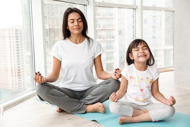 Vreedzame moeder en meisje die thuis mediteren, in lotusbloem zitten stellen op mat en het gebaar van yogamudra met vingers doen