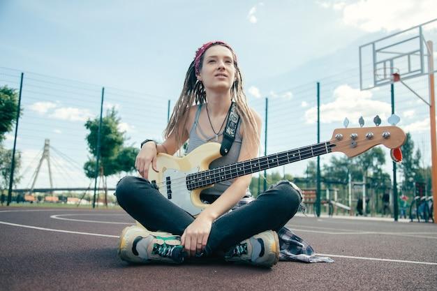 Vreedzame mooie dame met dreadlocks die vrijetijdskleding dragen en in de verte kijken terwijl ze met haar gitaar op het sportveld zit