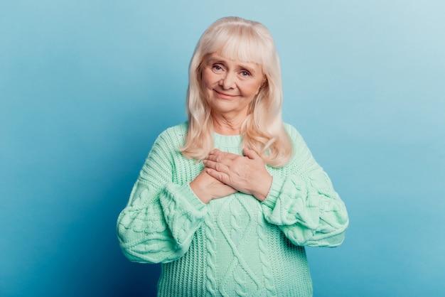 Vreedzame oude vrouw zet handen borst geïsoleerd over blauwe achtergrond