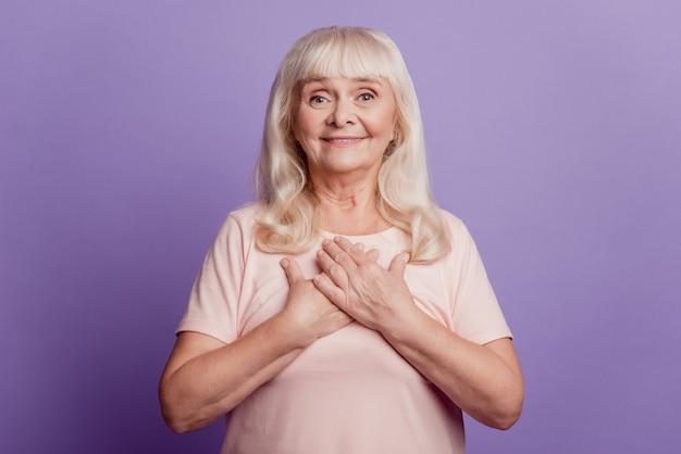Vreedzame oude vrouw zet handen borst geïsoleerd over violette achtergrond