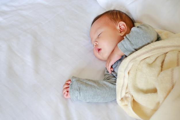 Vreedzame pasgeboren aziatische babyjongenslaap op bed met de deken.