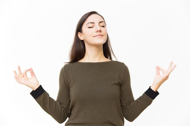 Vreedzame rustige vrouwelijke vrouw die zen gebaar maakt