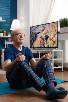 Vreedzame senior man die meditatietraining beoefent, comfortabel zit in lotuspositie met gesloten ogen op yogamat