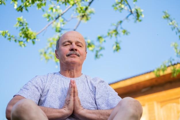 Vreedzame senior man zittend buiten onder de boom mediteren.