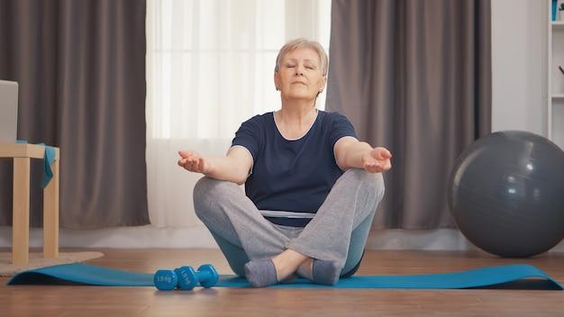 Vreedzame senior vrouw met gesloten ogen doet yoga in de woonkamer. actieve gezonde levensstijl sportieve oude persoon training workout thuis wellness en indoor training