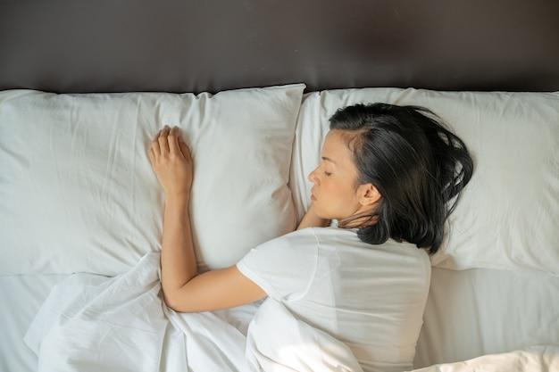 Vreedzame serene jongedame draagt pyjama's die op het bed liggen te slapen. bovenaanzicht