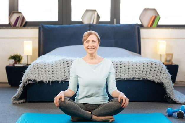 Vreedzame staat. vrolijke knappe volwassen dame die met gekruiste benen op blauwe yogamat zit met haar opgeruimd bed op de achtergrond