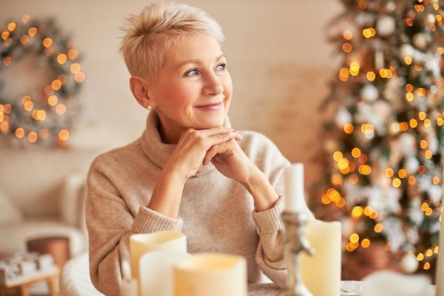 Vreedzame stijlvolle blanke vrouw van middelbare leeftijd in oversized trui met peinzende dromerige gezichtsuitdrukking, glimlachen, zittend aan tafel met kaarsen, wachtend op vrienden om kerstavond te vieren