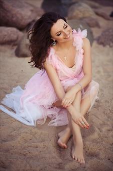 Vreedzame vakantie paradijs vrouw lopen op zonsondergang oceaan strand. meisje in het roze romantische kleding ontspannen op uitje van de luxe het tropische zomer.