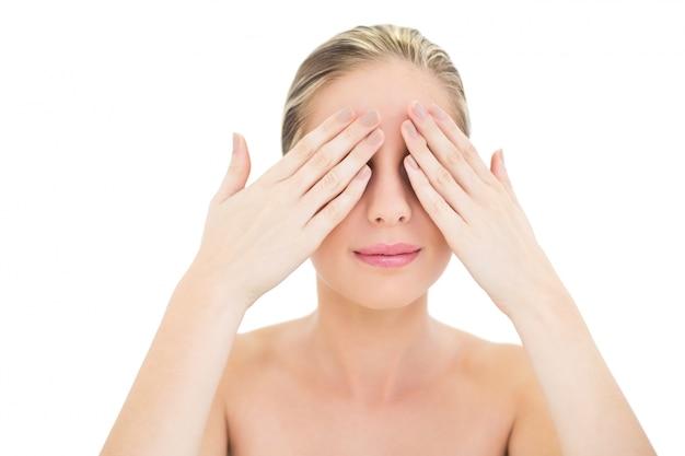 Vreedzame verse blonde vrouw die haar ogen behandelt