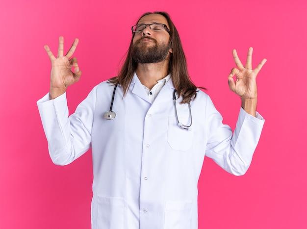 Vreedzame volwassen mannelijke arts met een medisch gewaad en een stethoscoop met een bril die een goed teken doet met gesloten ogen geïsoleerd op een roze muur