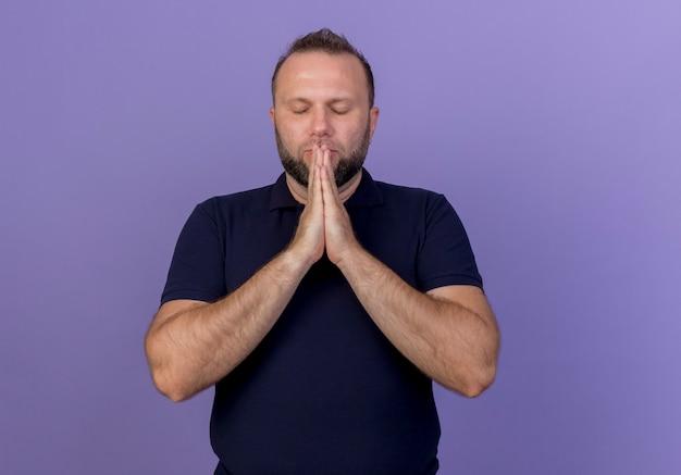 Vreedzame volwassen slavische man die handen in elkaar zet in de buurt van mond bidden met gesloten ogen geïsoleerd