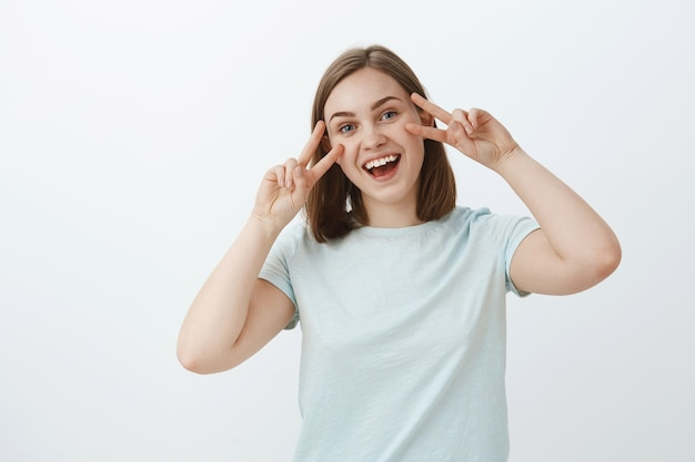 Vreedzame, vrolijke en vriendelijke knappe vrouw in trendy t-shirt met vredes- of overwinningstekens op gezicht en glimlachend in brede zin positieve en vrolijke vibes uit te drukken die geamuseerd staat over witte muur