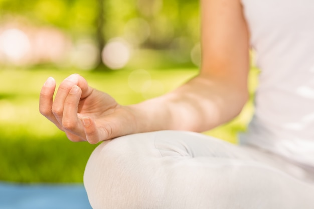 Vreedzame vrouw die yoga in het park op een zonnige dag doet