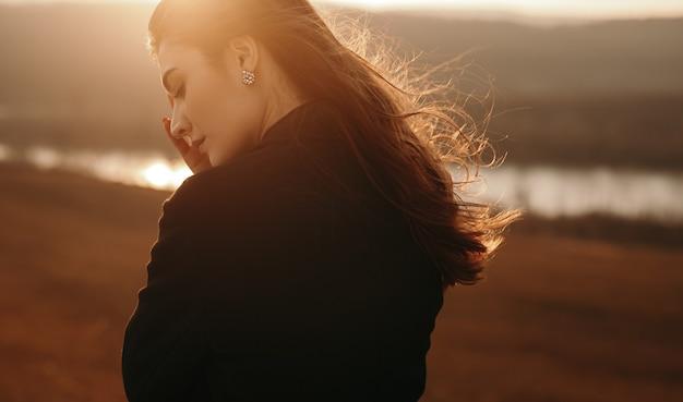 Vreedzame vrouw die zich dichtbij meer bij zonsondergang bevindt