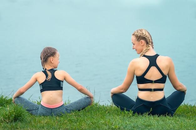 Vreedzame vrouw en haar dochtertje zitten in de buurt van het meer, kijken elkaar op groen gras